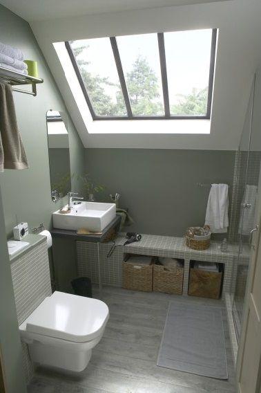 Une salle de bain sous comble n'est pas condamnée à un aménagement peu pratique. La preuve avec cette petite salle de bain de 4.5 m2. Lumineuse grâce au puits de lumière du toit elle optimise les astuces gain de place avec un plan de vasque plutôt qu'un meuble plus encombrant et un banc maçonné recouvert de faïence briquettes qui se prolonge dans l'espace douche. Le miroir au mur fait face à la porte vitrée de la douche pour un effet d'agrandissement total de la salle de bain.
