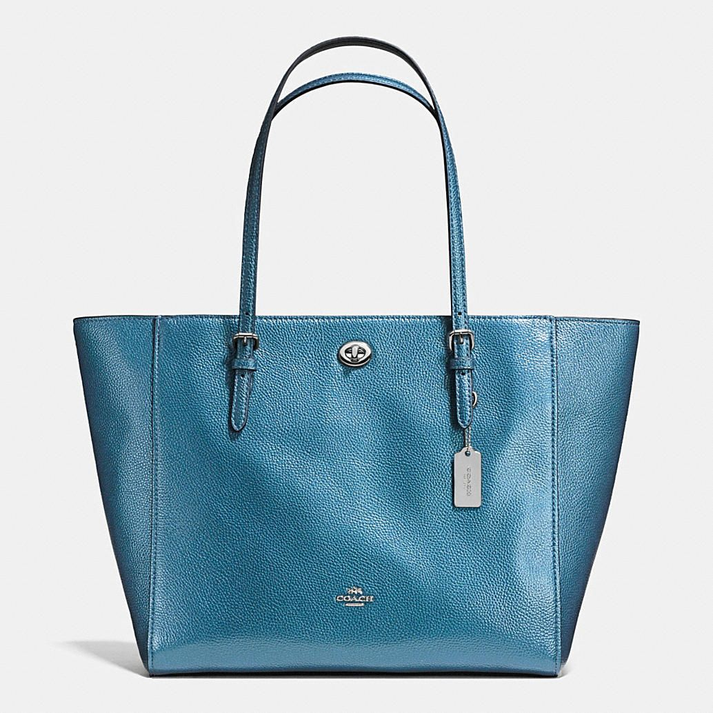 Metallic pebble leather adds subtle texture and a soft glow to an effortless, go-anywhere tote. A polished metal hangtag and a hidden pocket secured with a petite turnlock add a quintessential Coach finish to its hand-assembled design.