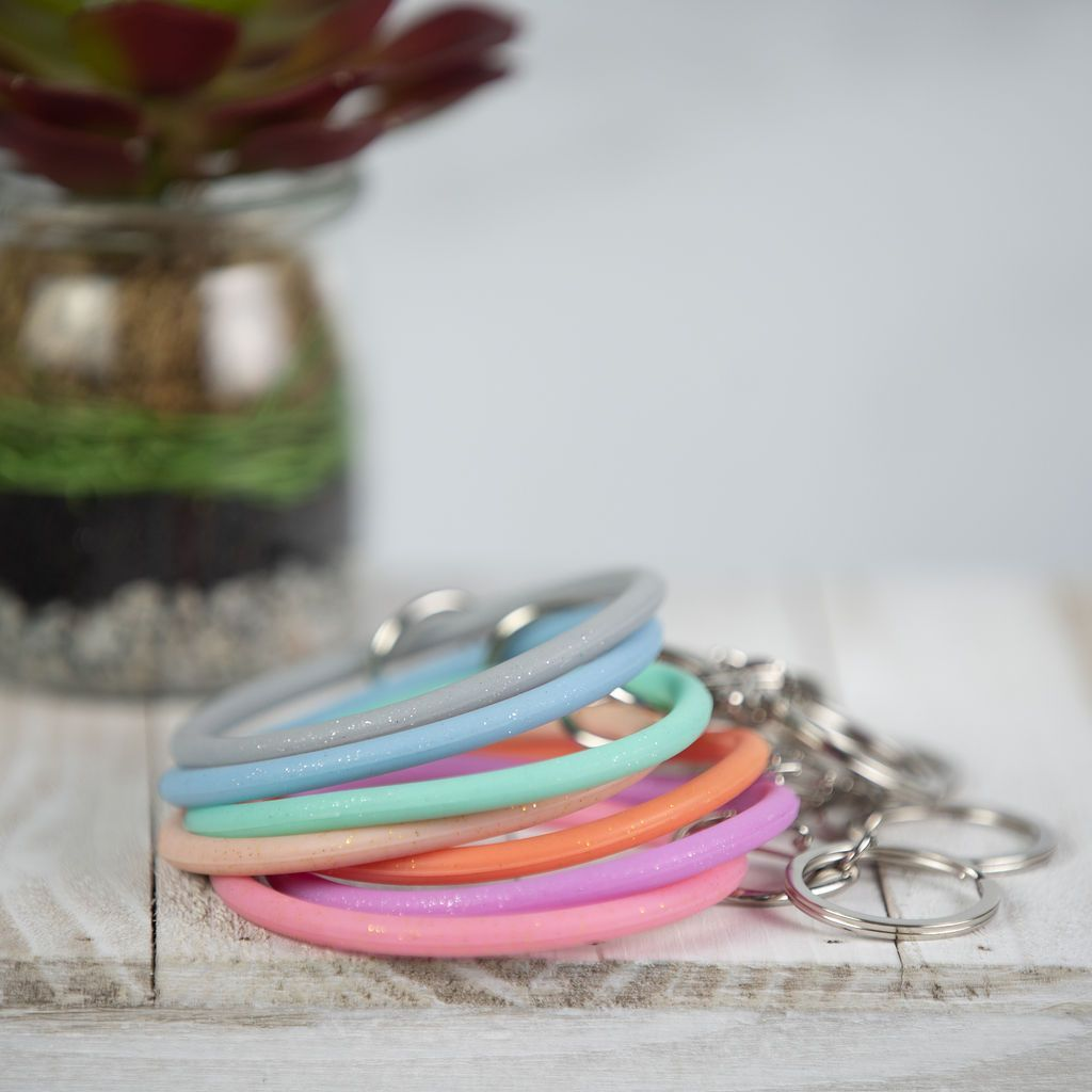 This slim profile silicone bracelet keychain is ideal for anyone that is in the go and needs to have their keys easily accessible. The super slim bracelet allows it to slip over the hand and on the arm of most. The silicone bracelet is infused with gorgeous glitter to give it a bit of sparkle. The key ring can clip on or off, and is made of stainless steel for strength and durability.