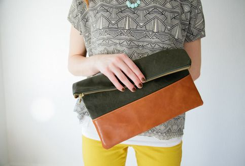 A stunning clutch made out of heavy army green waxed canvas and genuine leather. A chunky gold zipper closure.   Big enough for all your essentials plus your ipad (or kindle.. ect)    Note: Each clutch is slightly different since no two pieces of leather are identical.       **Very limited quantity.