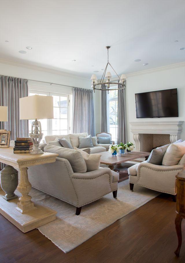 3 sofas around a fireplace and TV