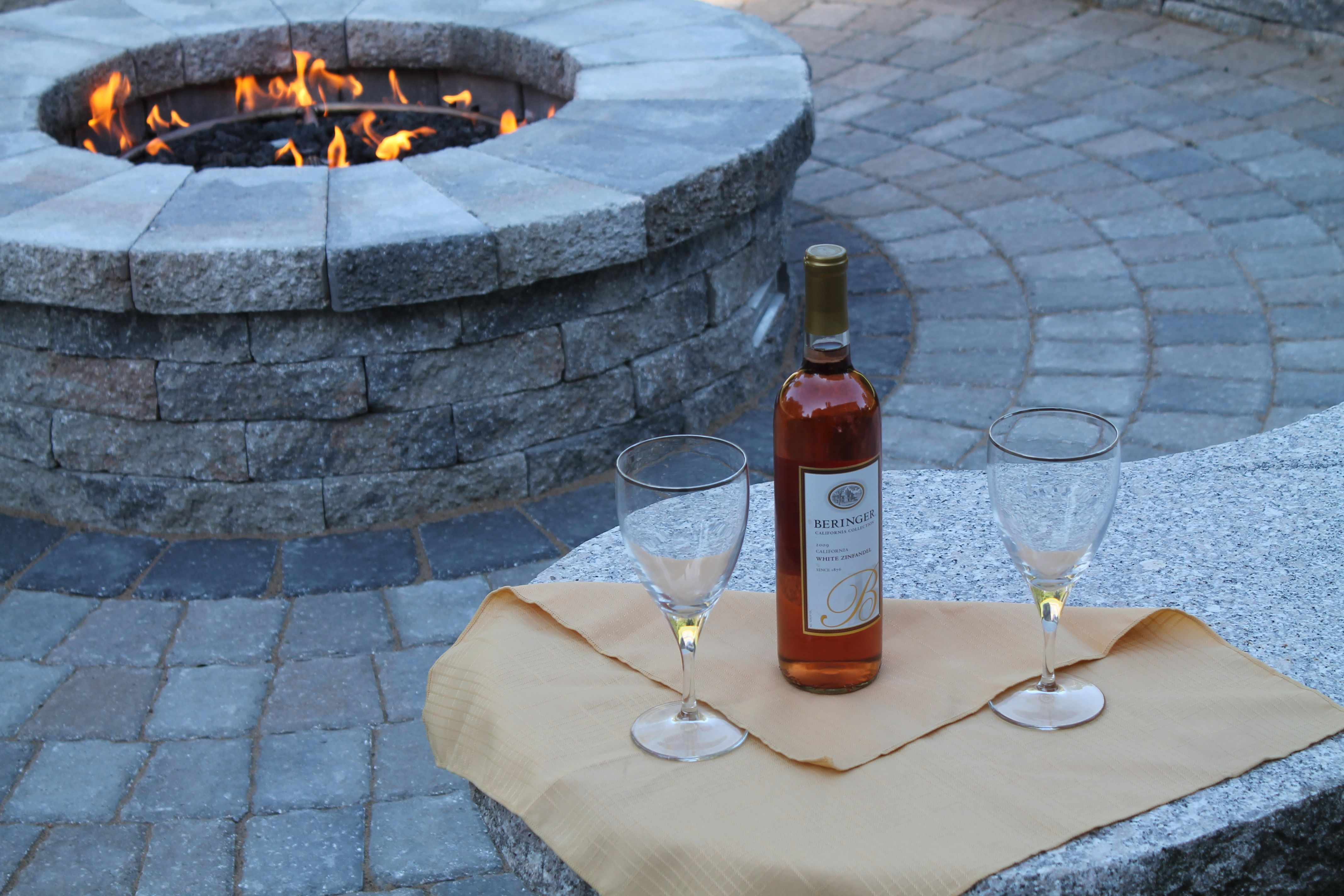 Gas fire pit in a paver patio with a granite bench installed by