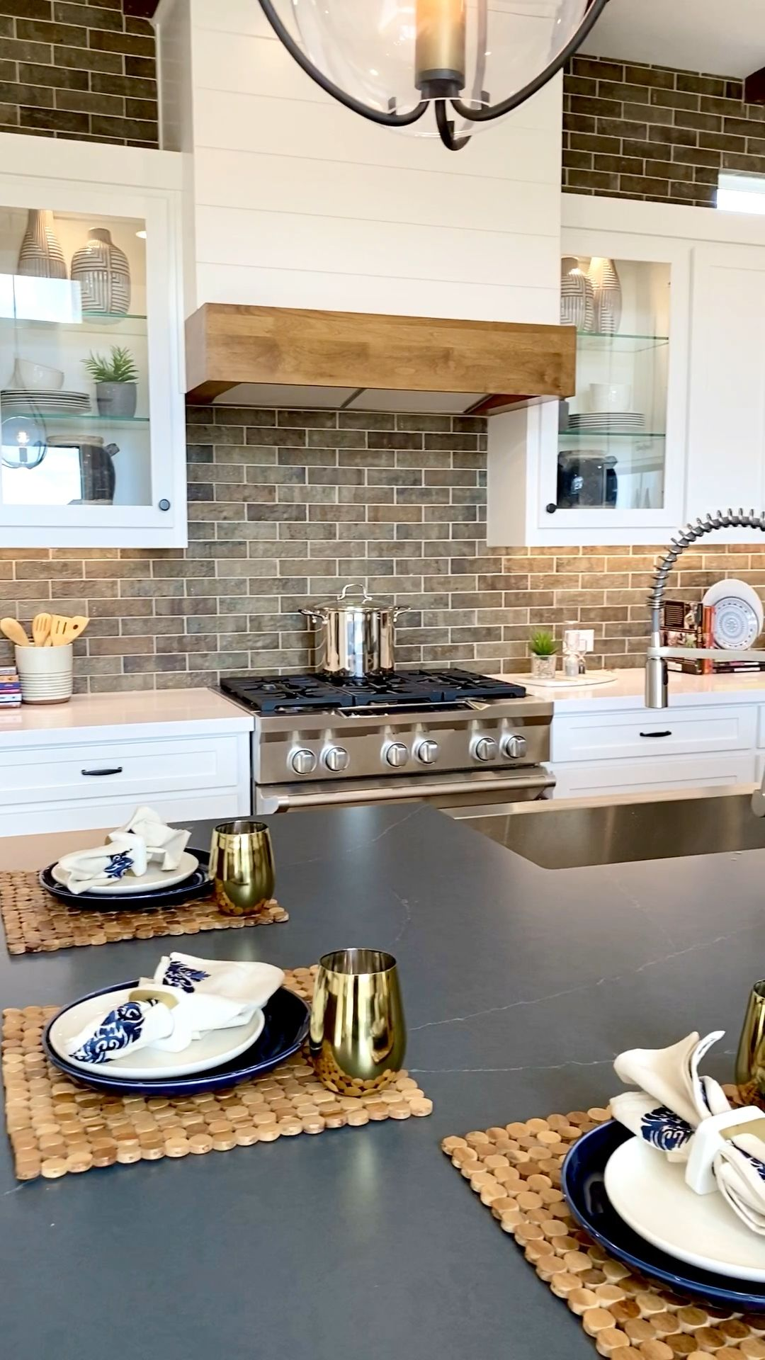 A blend of the classic white kitchen with a modern-industrial accent using a brick backsplash!  Great design for many styles - Click to see more model home photo inspiration images.... THE DECORATING COACH  #decoratingideas #kitchenideas #brickwall