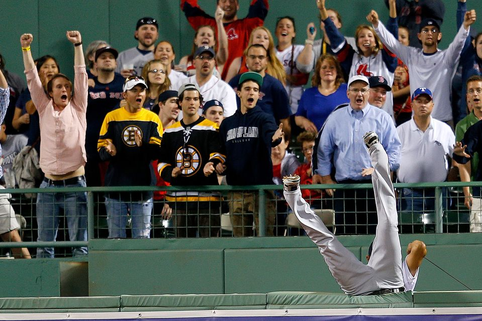 LONG BALL: Nelson Cruz of the Texas Rangers leapt over the right field wall but was unable to catch a home run hit by Mike Carp of the Boston Red Sox at Fenway Park in Boston Tuesday. (Jim Rogash/Getty Images)