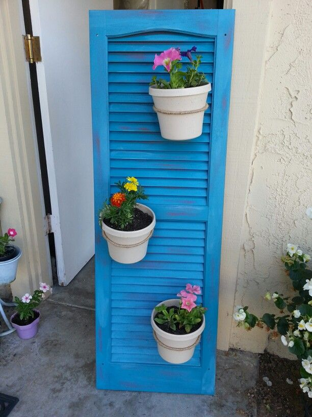 Use an old shutter to hang flower pots. Flower pots are attached ...