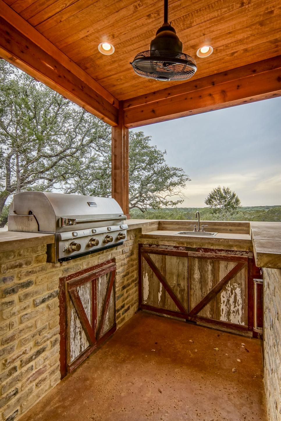 Neutral Brick And Barn Like Cabinet Doors Create The Perfect Foundation For A Country Desi Outdoor Kitchen Design Outdoor Kitchen Outdoor Kitchen Design Layout