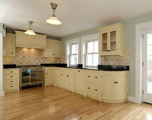 Cream fitted cupboards with black granite worktops in contemporary kitchen with wooden floor remodel ideas pinterest granite worktops black granite