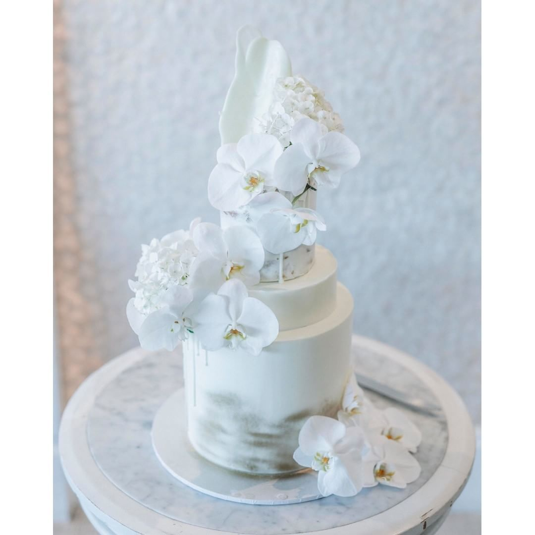 White buttercream and fresh orchids on this elegant wedding cake