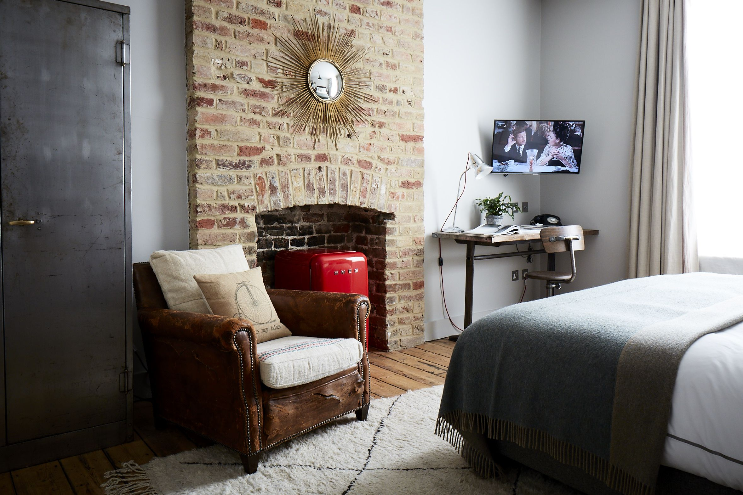 Medium room at artist residence london featuring a vintage leather club chair red smeg mini
