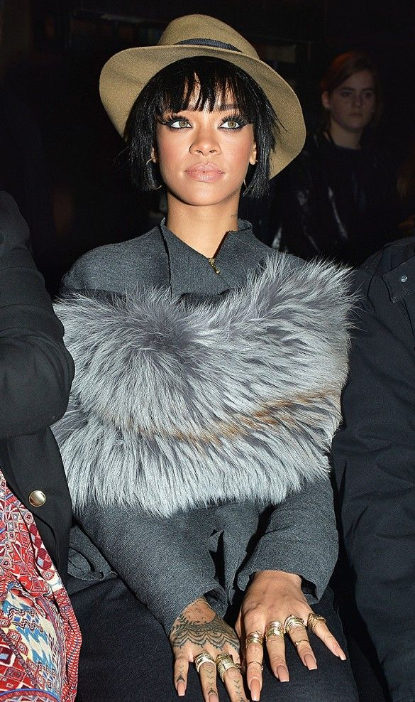 Rihanna in a charcoal fur wrap and green hat.