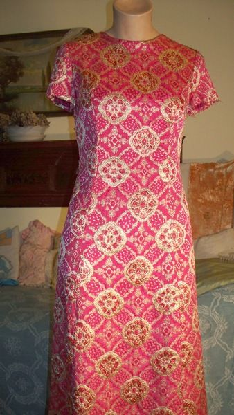 Dark pink and gold gown, shiny and glitzy. Has vertical seams over bust and down the front of the gown. No seam at waist. Lined in soft acetate, metal zipper down the back.