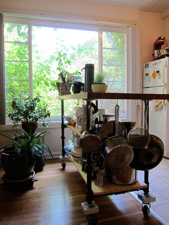 Could make an island myself like this one...painted plumbing pipe, shelves of oiled pine, hooks for storage, butcher block.  with this, could overhand for table somewhat.