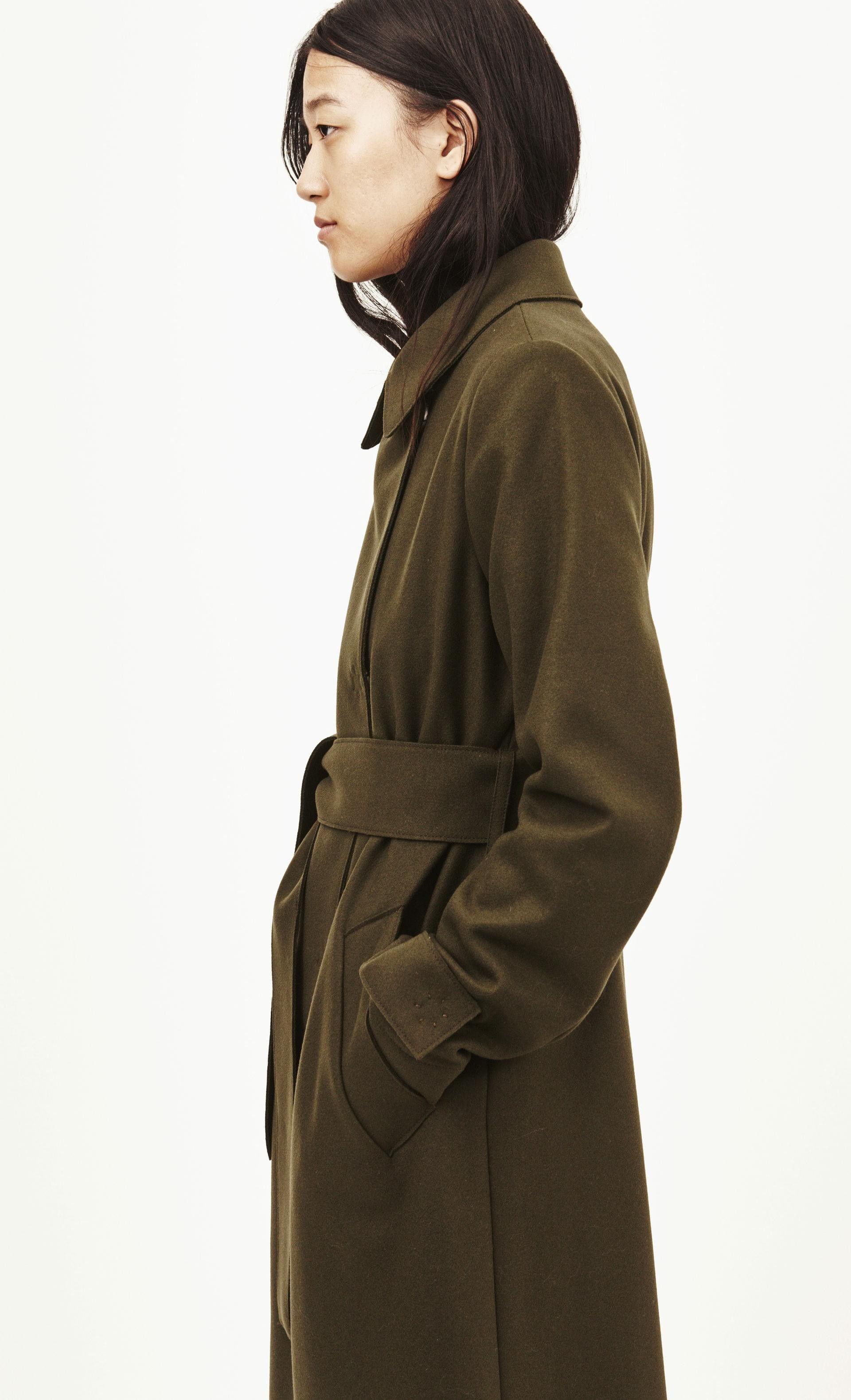 Kaksirivinen takki on villa-polyamidisekoitetta, ja siinä on piilopainonapit. Leikkaus on hieman levenevä, helma ulottuu polviin ja takana on halkio. Siinä on vuori ja viistot halkiotaskut, ja mukana tulee vyö. Laakaommellut reunat on leikattu laserilla.