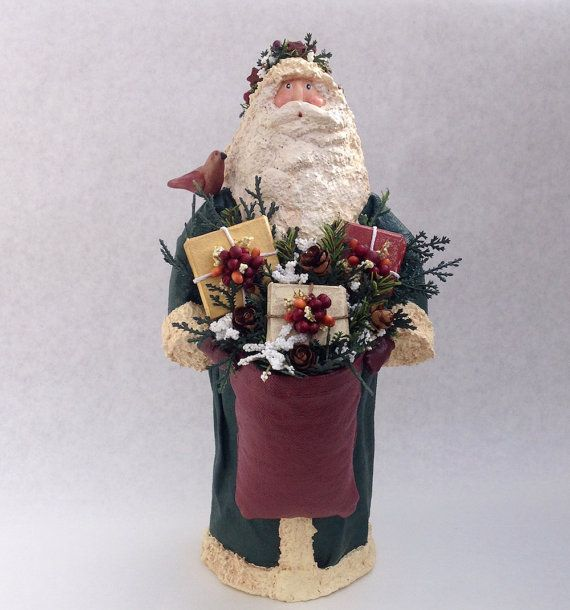 This Dark Forest Green Santa Claus Figurine inspires the spirit of giving gifts at Christmas. This Santa has a Folk Art, Primitive style but has a very traditional theme. Santa carries three packages that were dry brushed in red, gold and ivory. Each package is wrapped in white cording and is adorned with various pretty berries. A friendly winter bird sits on his shoulder. His hood is accented with a holly garland accented with clay stars and various berries. This Santa is one of a kind in…