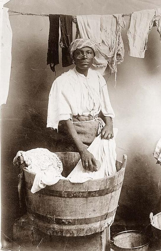 black woman washing clothes by hand in an old wooden tub