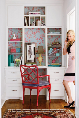 I like how they used this small space for an office. l like the wallpaper behind the shelves.