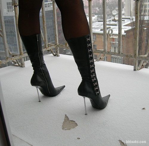 Fashion designer boots with metal heels and snow.