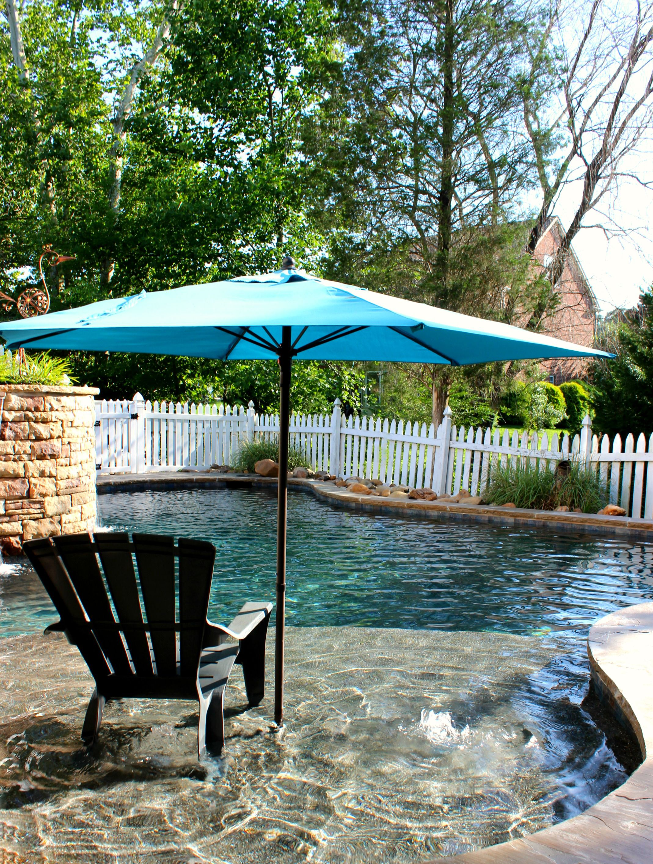 Tanning ledge with bubblers and umbrella stand featured in a ...