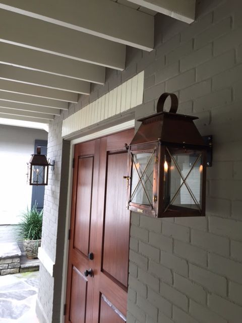 Double Bevolo Coach House Lanterns Add A Cozy Touch To This Brick Home