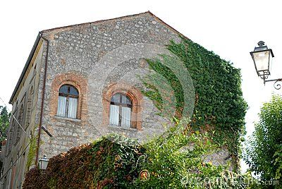 Photo made in Monselice ancient medieval village that is located in the park of the hills Hills in Veneto (Italy). In the image you see the side partially covered with ivy and part of the facade of an old house built in blocks of rock. On the wall next to open two beautiful arched windows with white curtains. Right to a lamppost by a romantic touch to the picture.