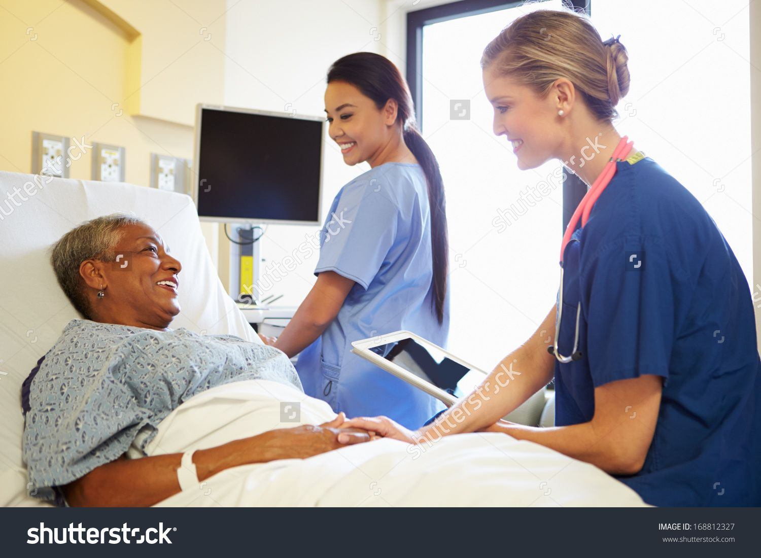 Nurse With Digital Tablet Talks To Woman In Hospital Bed