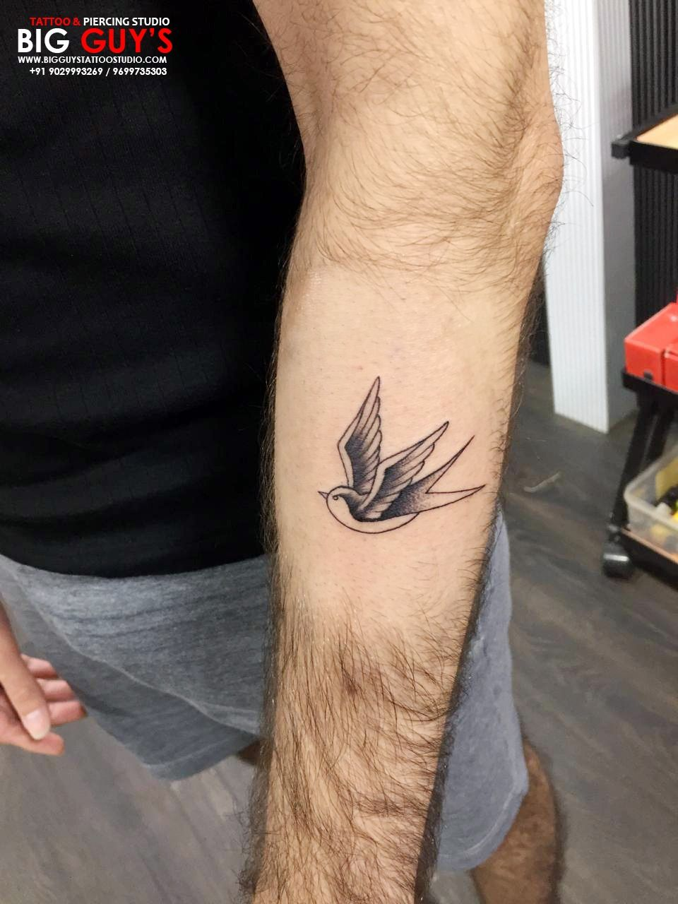 Bird tattoo made on wrist of boy with black ink and inque