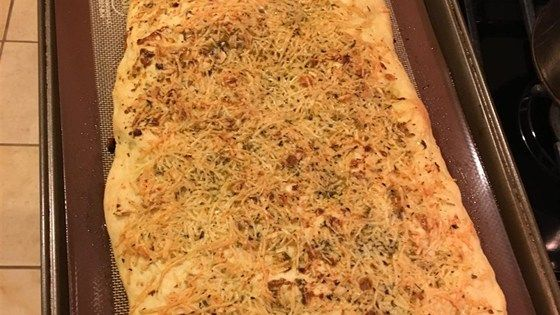 Deliciously easy focaccia topped with garlic-infused olive oil, cheese, and herbs will be ready in 1 hour with this bread machine recipe.