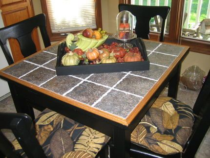 tile on an old kitchen table. Might have to do this for a craft ...