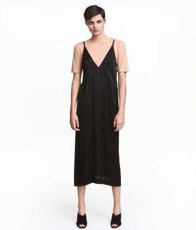 Zwart. Een knielange jurk van zacht satijn met een V-hals, smalle schouderbandjes en een naad onder de borst. Gevoerd lijfje.