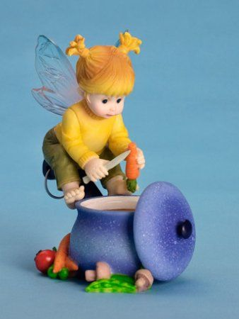 This little pixie knows the perfect recipe for a cold-weather day-- vegetable soup! The fairy slices a carrot into the pot, and more ingredients lie around the base of the crock. The perfect little friend to make you feel warm and happy inside!