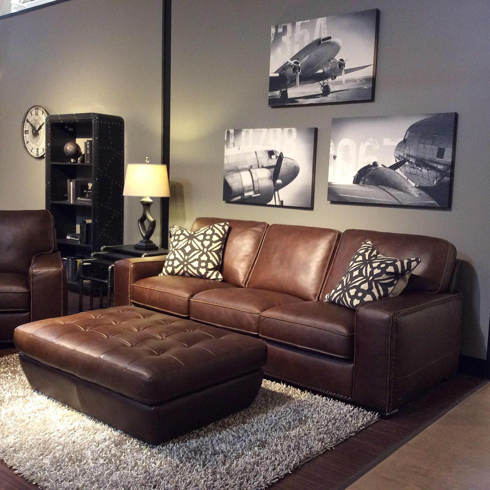 Family room with warm gray walls, black and white art, brown leather ...
