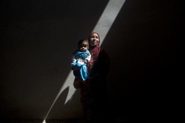 SYRIE, Saraqib : Amina, une femme syrienne qui a fui les combats d'Alep, est photographié à l'intérieur d'un bâtiment abandonné avec son fils de cinq mois, le 9 Septembre 2013. Le président américain Barack Obama et son homologue russe Vladimir Poutine ont convenu de placer les armes chimiques syriennes sous contrôle international lors du sommet du G20 la semaine dernière à Saint-Pétersbourg. AFP PHOTO / GIOVANNI Diffidenti