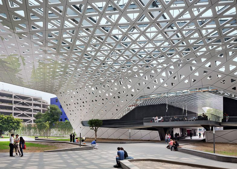 An aluminium canopy speckled with triangular perforations shelters the space between old and new buildings at Mexico's National Film Archive and Film Institute