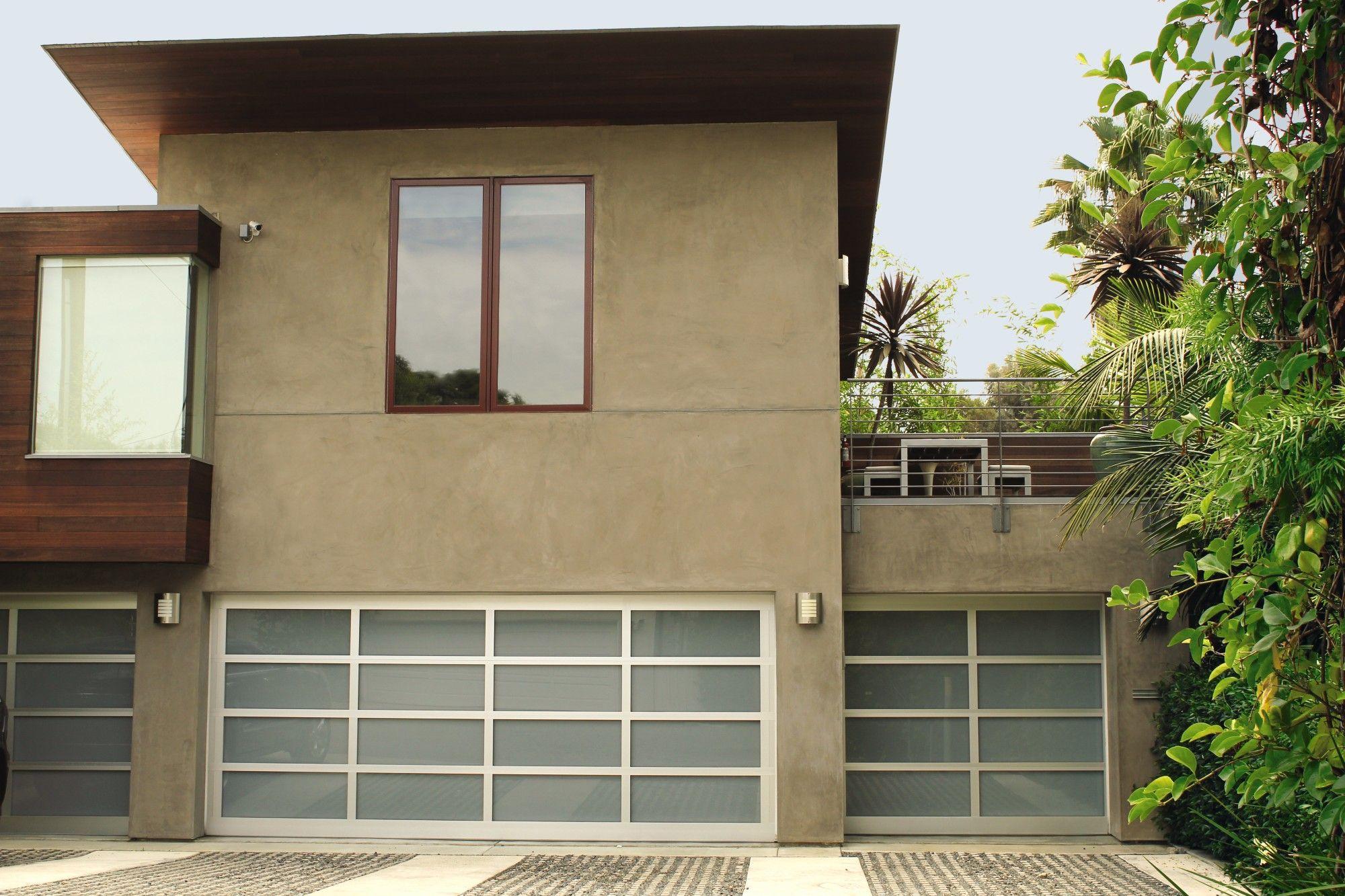Glass aluminum garage door on this modern home Modern Home Design