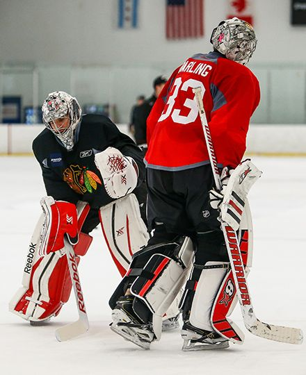 Corey Crawford and Scott Darling share a moment at Monday's practice.