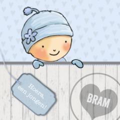 Leuk winter geboortekaartje met jongetje met muts op en hip blauw label met naam voorop.
