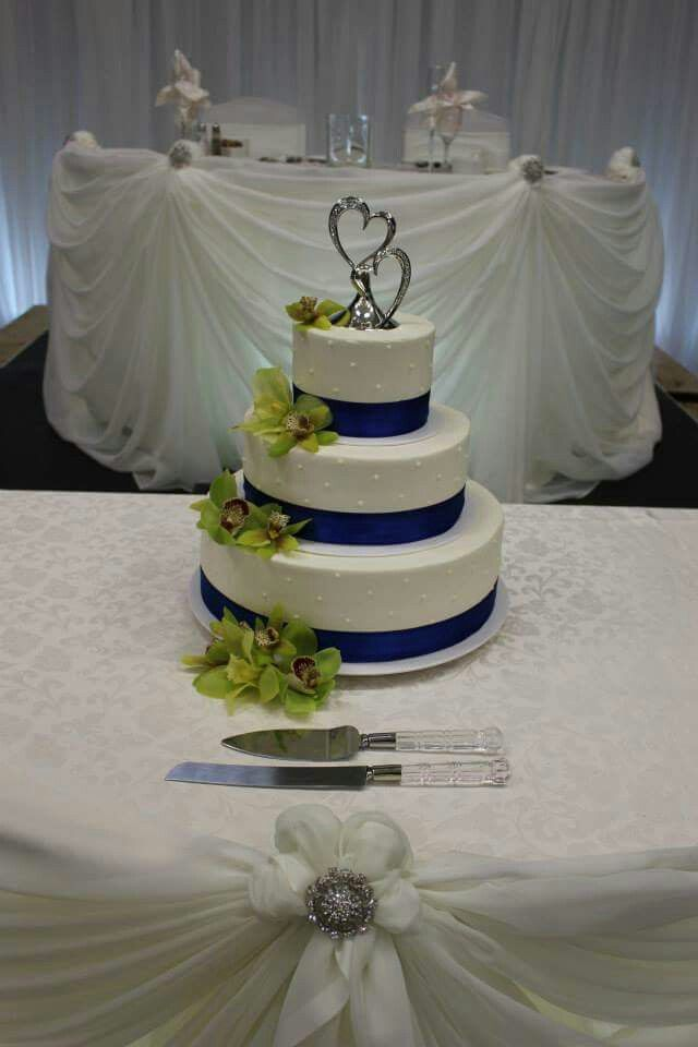 3-tier wedding cake with a simple design of dots, wrapped with royal blue satin ribbon, adorned with fresh green orchids and topped with a double heart ornament. www.mitchels.ca #wedding #weddingcakes #3tier #flowers #simple #royalblue