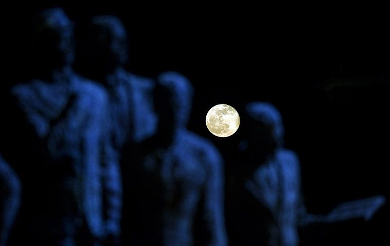 Skopje, Macedonia: a full moon rises behind the sculpture Gemidzii in the capital cityPhotograph: Robert Atanasovski/AFP