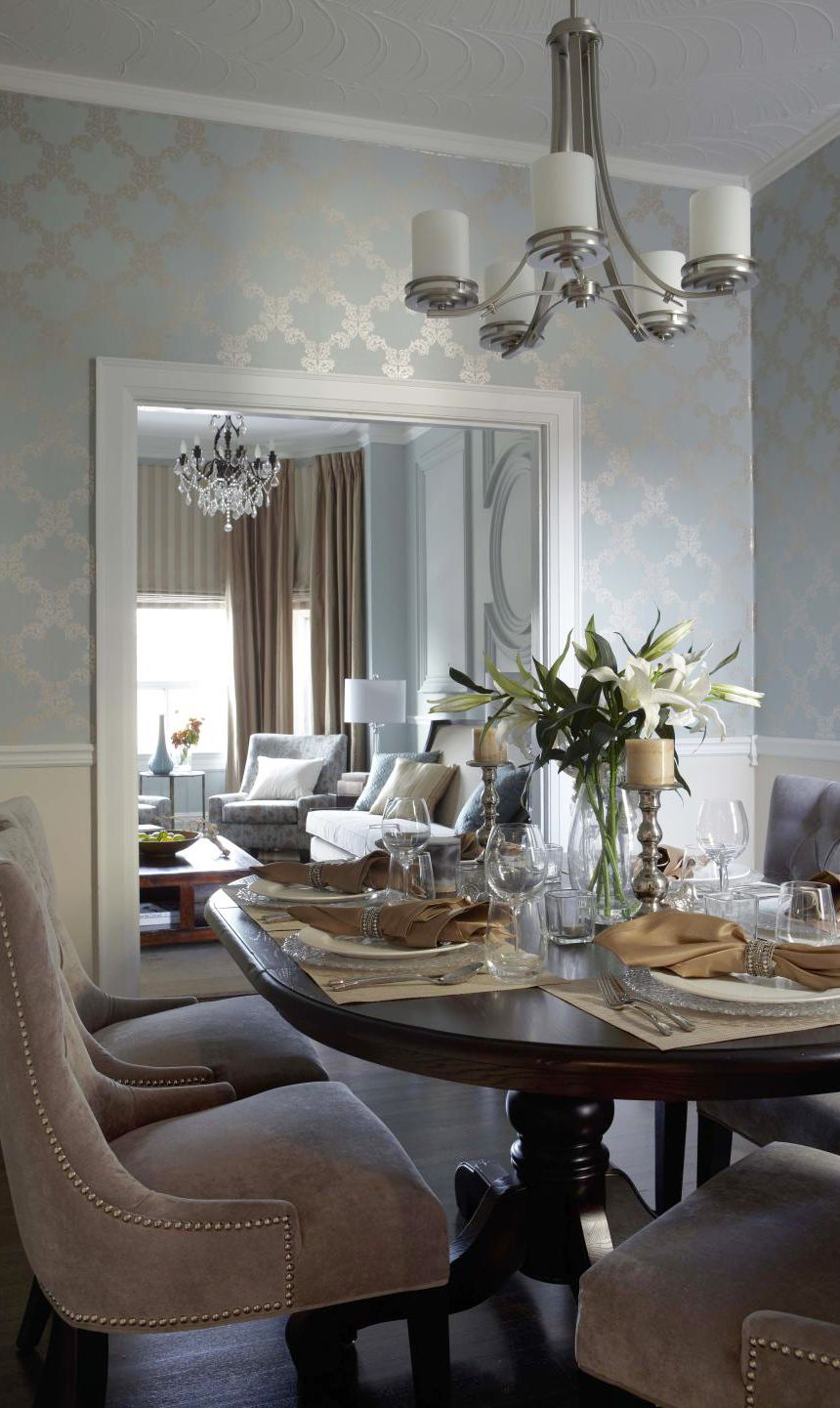 Contemporary dining fixture in brush nickel finish and traditional crystal chandelier in bronze finish in living room.  Love the wallpaper!