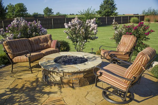 Elevated outdoor living area and fire pit surrounded with landscaping by Red Valley Landscape & Construction.