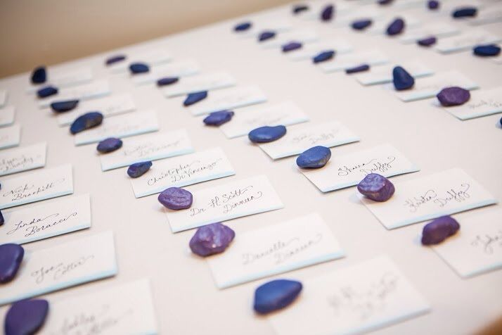 Mini envelopes edged in watercolor, hand lettered by strawberry small works studio. Inside are purple and blue paper leaves with the table numbers. And painted rocks!!