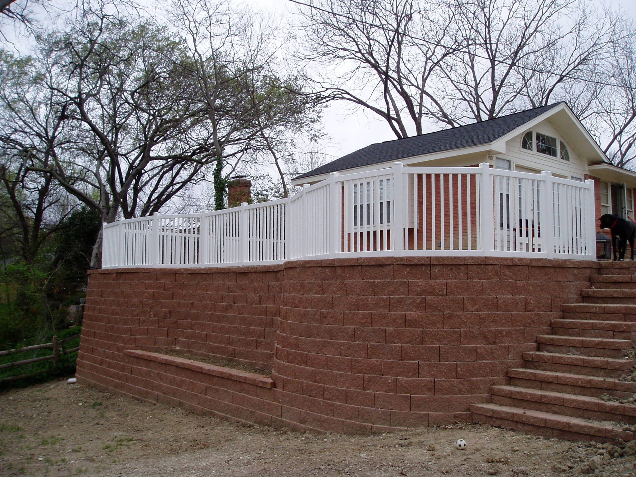 If you need a retaining wall we can build it and put a vinyl fence
