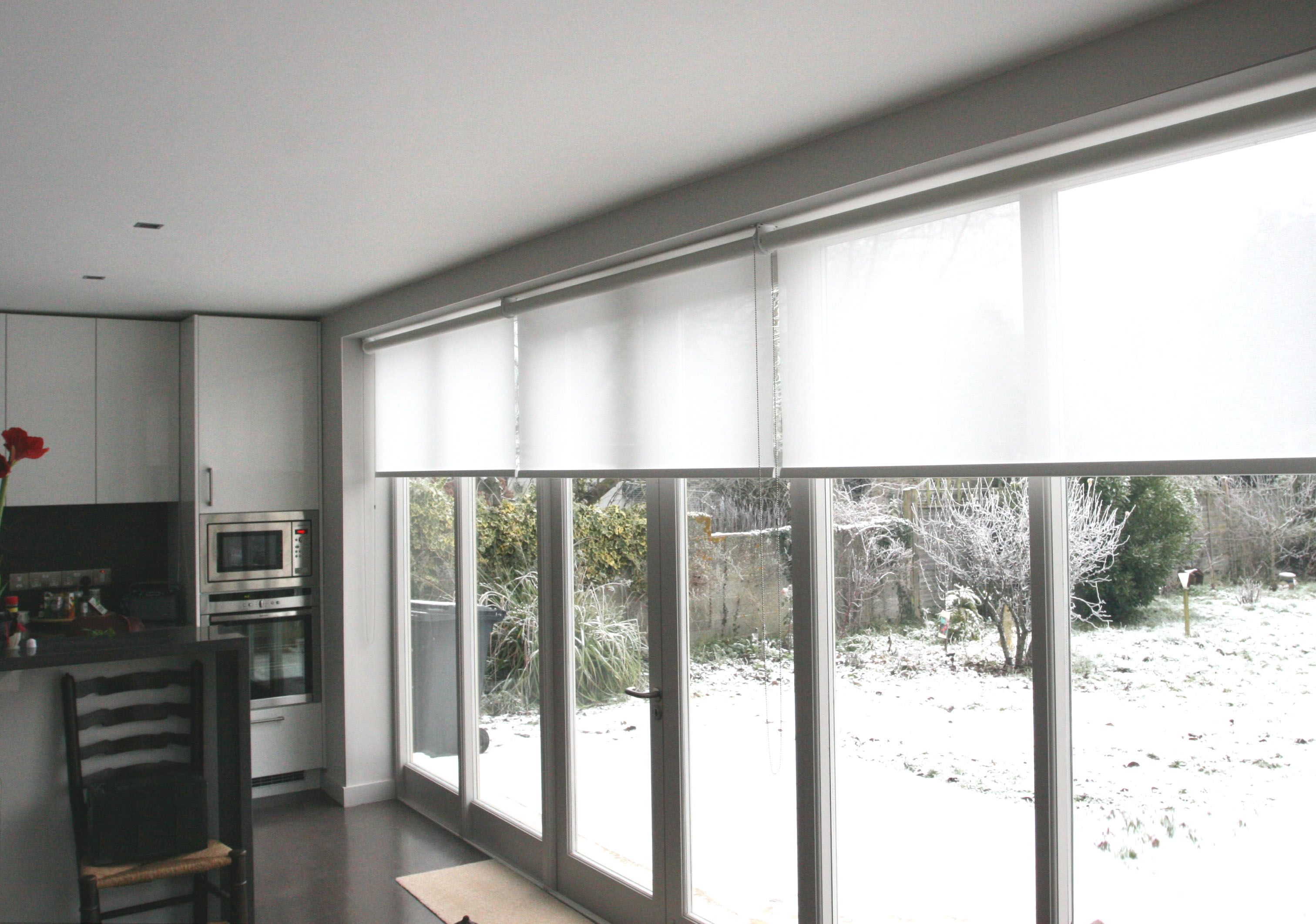 Roller blinds in hessian white fitted with bifold doors to reduce