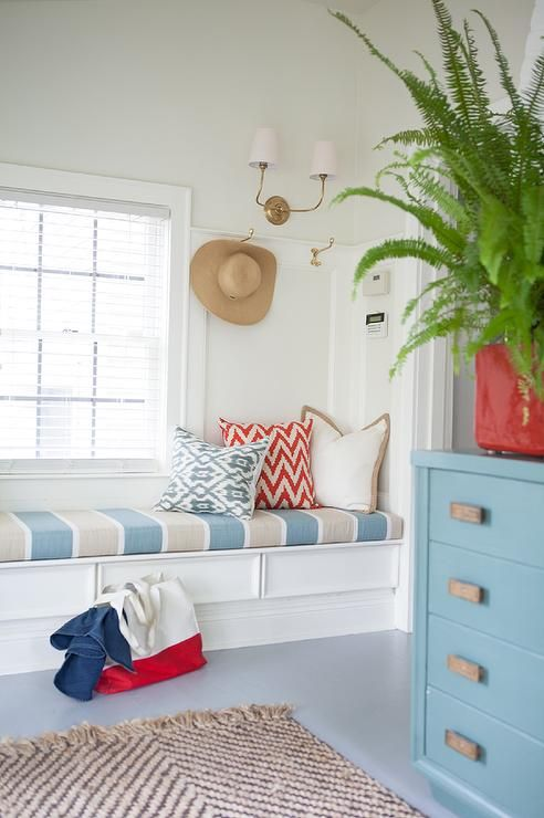 Cottage mudroom features a long built in bench adorned with a blue and gray striped cushion placed under brass hooks illuminated by a Vendome Double Sconce in Antique Brass alongside a jute rug layered atop a blue painted floor.