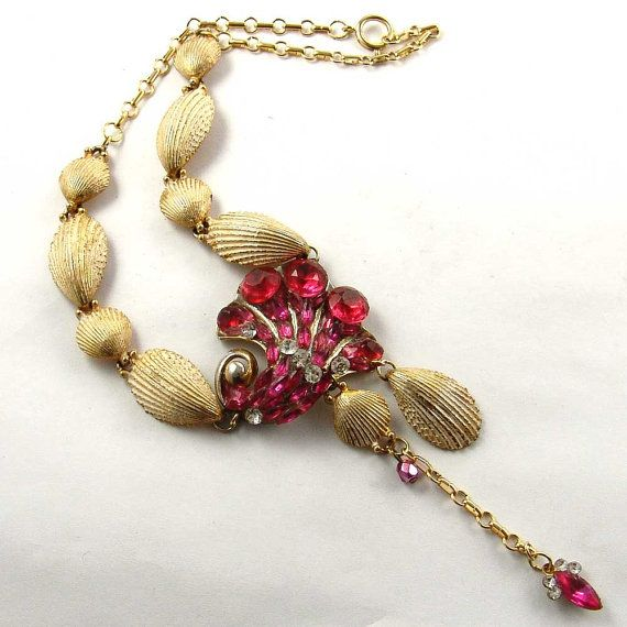 This is an up-cycled piece with vintage jewelry with rhinestones. The centerpiece has been modified with additional fuchsia red vintage rhinestone crystals. The original shell necklace has been upcycled and redesigned. Centerpiece Size: 2 x 3    Chain length: 19    This OOAK necklace is designed, constructed, and signed by Kay    SKU: E1484