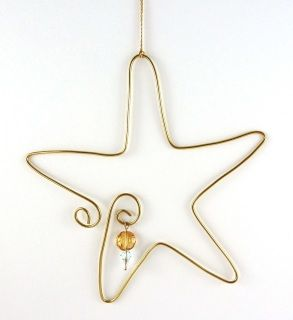 The Holiday Ornament for 2013 is an original design carefully worked in tarnish resistant gold-colored wire and graced with three crystal beads that sparkle softly.  It hangs from a golden thread. $15.00