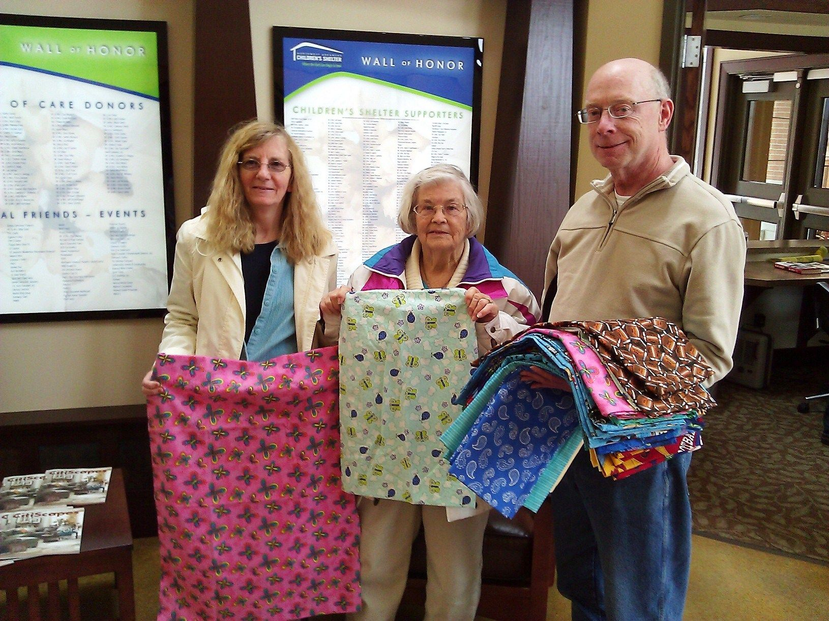 PRETTY PILLOWCASES -- Bernice Hunt (from left) of Bella Vista, Alma Dickson of Lawton, Okla. and Stephen Hunt of Bella Vista show off some of the 32 original pillowcases they made and donated to the kids at Northwest Arkansas Children's Shelter. The Children's Shelter has to provide everything our kids need for up to 45 days, including bedding, so we very much appreciate the creativity, thoughtfulness and tender loving care that went into this heart-felt and very practical donation!