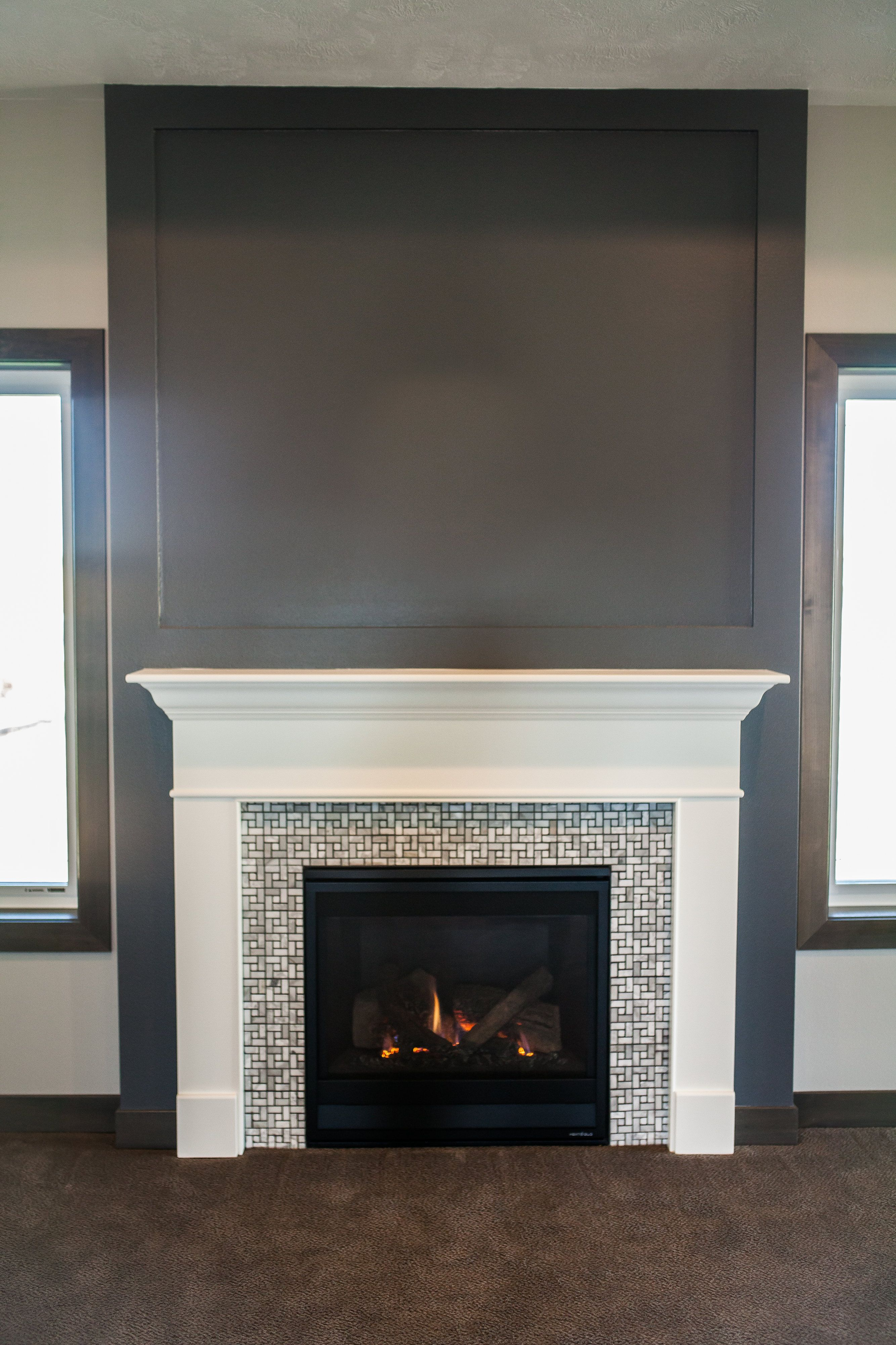 White painted mantle and glass tile fireplace surround also