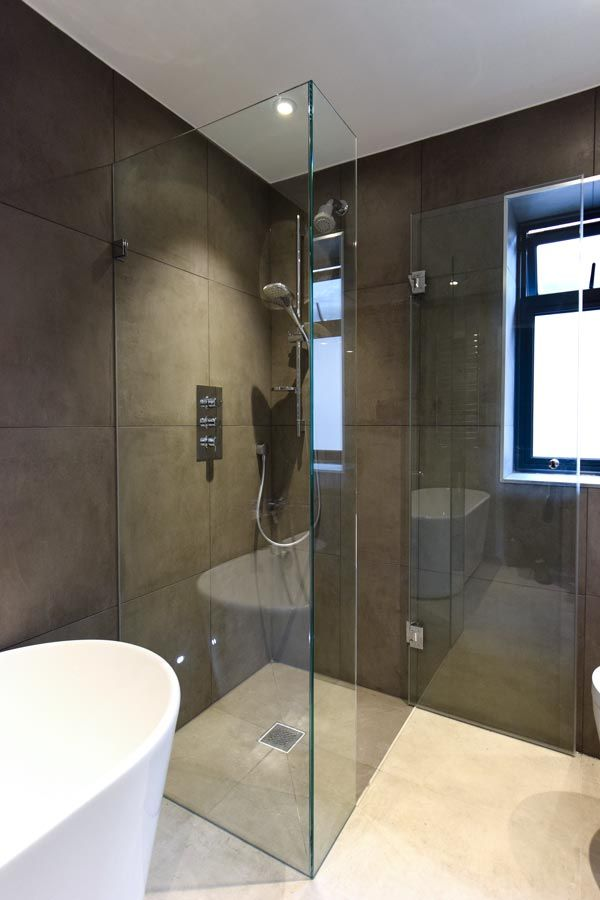 Frameless shower enclosure with polished chrome hinges and a ...