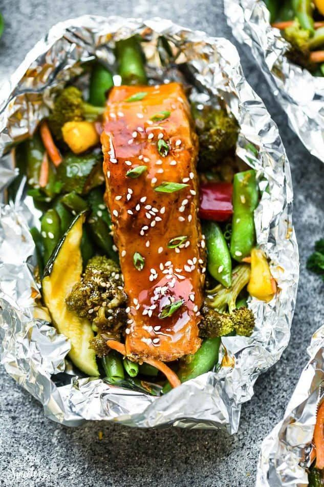This recipe for Teriyaki Salmon Foil Packets with Vegetables is the perfect easy campfire or weekly dinner for summer. A complete meal with practically no clean up and full of your favorite sweet and savory Asian-inspired meal with perfectly tender and flaky salmon, edamame, broccoli, pineapple and red bell pepper. Make a batch for Sunday meal prep and pack it up for your lunchbox or lunch bowls. Foil packets are great for camping or busy weeknights. #teriyakisalmon